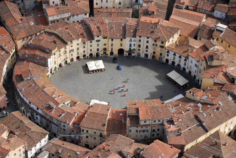 Piazza dell'Anfiteatro, Lucca. Le case sono costruite sugli antichi spalti, mentre gli affacci sulla piazza seguono ancora l'andamento delle arcate di accesso all'arena.